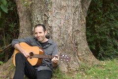 Усмехаясь человек тренькая гитарой под деревом Стоковые Фотографии RF