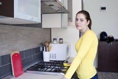 Усмехаясь чистка девушки на кухне Стоковые Изображения