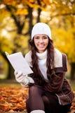 Усмехаясь чтение женщины в парке Стоковые Изображения RF