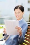 Усмехаясь чтение коммерсантки завертывает в бумагу outdoors Стоковое Изображение RF