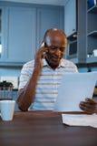 Усмехаясь чтение человека документирует пока использующ телефон дома стоковая фотография rf