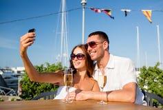 Усмехаясь шампанское пар выпивая на кафе Стоковая Фотография RF
