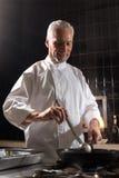 Усмехаясь шеф-повар варя в кухне ресторана Стоковое Изображение