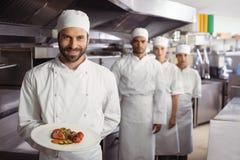 Усмехаясь шеф-повар держа очень вкусное блюдо в кухне Стоковое фото RF