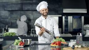 Усмехаясь шеф-повар играя с перечницей на рабочем месте Счастливый работник подготавливая сварить сток-видео