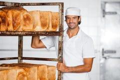 Усмехаясь шкаф хлеба мужского хлебопека готовя стоковая фотография rf
