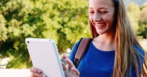 Усмехаясь школьница используя цифровую таблетку в кампусе акции видеоматериалы