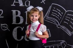 Усмехаясь школьница стоя перед доской как предпосылка с рюкзаком на ей назад Увеличенный взгляд стоковые фотографии rf