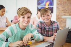 Усмехаясь школьники работая на электронном проекте в классе Стоковые Изображения