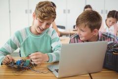 Усмехаясь школьники работая на электронном проекте в классе Стоковое Изображение