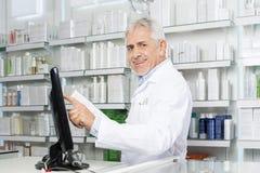 Усмехаясь экран монитора аптекаря касающий в фармации Стоковые Изображения RF