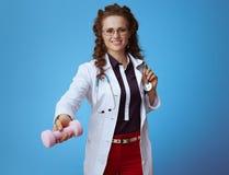 Усмехаясь элегантная женщина врача давая гантель на сини стоковое фото rf