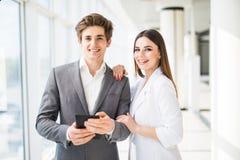 2 усмехаясь элегантных бизнесмены человека в официально костюме и женщины в куртке и платье смотря что-то на цифровой таблетке вн Стоковая Фотография