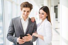 2 усмехаясь элегантных бизнесмены человека в официально костюме и женщины в куртке и платье смотря что-то на цифровой таблетке вн Стоковое Изображение RF
