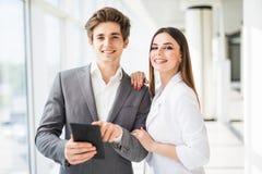 2 усмехаясь элегантных бизнесмены человека в официально костюме и женщины в куртке и платье смотря что-то на цифровой таблетке вн Стоковые Фото