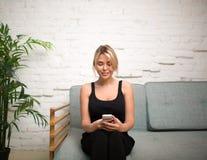 Усмехаясь электронная почта чтения девушки битника на портативном телефоне клетки, усаживании на кресле в доме Стоковые Фото