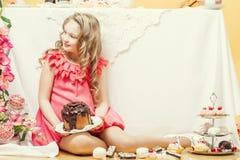 Усмехаясь элегантная девушка представляя с вкусными тортами Стоковые Фотографии RF