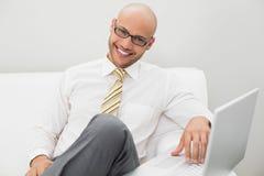 Усмехаясь элегантный бизнесмен используя компьтер-книжку на софе дома Стоковая Фотография