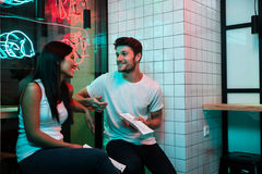 Усмехаясь любящие пары сидя в кафе держа меню ресторана Стоковое Изображение
