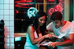 Усмехаясь любящие пары сидя в кафе держа меню ресторана Стоковые Фотографии RF