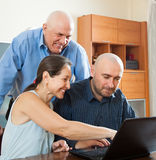 Усмехаясь люди на работе на компьтер-книжке стоковые фотографии rf