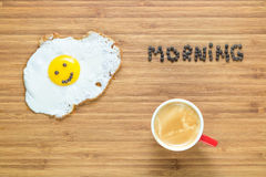 Усмехаясь яичница лежа на деревянной разделочной доске с надписью утра около ее Классическая концепция завтрака Стоковые Изображения RF