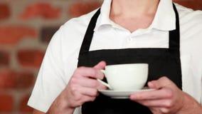 Усмехаясь barista вручая чашку кофе видеоматериал