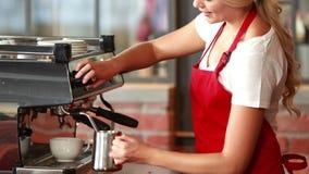 Усмехаясь barista испаряясь молоко на машине кофе сток-видео