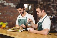 2 усмехаясь baristas работая на счетчике Стоковые Изображения RF