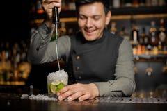 Усмехаясь cachaca бармена лить в стекло коктеиля процесс стоковое фото