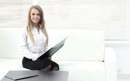 Усмехаясь clipbord работника сидя в современном офисе Стоковые Изображения RF