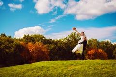 Усмехаясь groom держа счастливую невесту на поле стоковая фотография