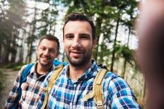 Усмехаясь hikers принимая selfie совместно в древесины Стоковые Фотографии RF