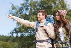 Усмехаясь hikers с рюкзаками указывая палец Стоковая Фотография