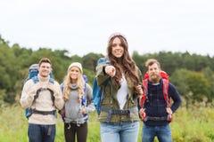 Усмехаясь hikers с рюкзаками указывая палец Стоковое Изображение