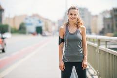 Усмехаясь jogger женщины стоя все еще на мосте Стоковые Фотографии RF