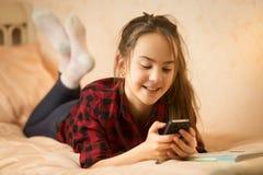 Усмехаясь ling девочка-подростка на кровати и использовании smartphone Стоковая Фотография
