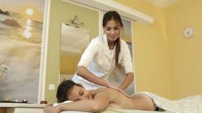 Усмехаясь masseuse и счастливый женский клиент действуя вверх для камеры видеоматериал