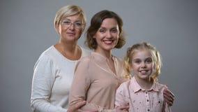 Усмехаясь multigeneration женщины на серой предпосылке, соединении семьи, люб акции видеоматериалы
