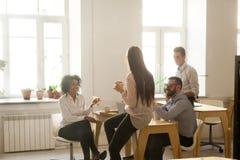 Усмехаясь multiracial коллеги говоря пока ел пиццу на  Стоковая Фотография RF