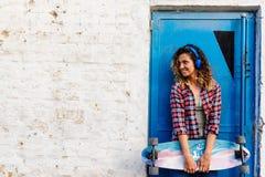 Усмехаясь skateboarding девушка стоя в улице держа скейтборд длинн-доски Стоковые Изображения