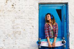 Усмехаясь skateboarding девушка стоя в улице держа скейтборд длинн-доски Стоковая Фотография