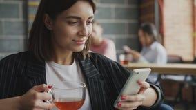 Усмехаясь smarpthone женского предпринимателя занимаясь серфингом и выпивая чай пока имеющ пролом в занятом офисе сток-видео