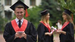Усмехаясь smartphone мужчины постдипломный держа и смотреть в камеру, градацию сток-видео