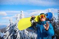 Усмехаясь snowboarder представляя сноуборд нося на плечах на лыжном курорте около леса перед встречей freeride Всадник стоковое фото rf
