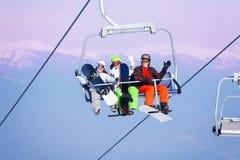 3 усмехаясь snowboarders сидя на ropeway Стоковое Изображение
