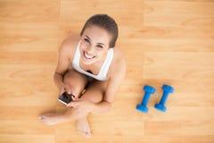 Усмехаясь sporty брюнет держа мобильный телефон и сидя рядом с гантелями стоковые изображения rf