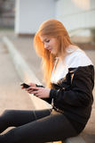 Усмехаясь sporty девушка с smartphone стоковое изображение