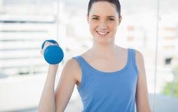 Усмехаясь sporty женщина работая с гантелью стоковая фотография