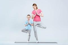 Усмехаясь sporty йога матери и дочери практикуя совместно, йоги Vrikshasana представление или представление дерева Стоковые Фото